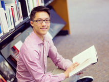 Happy male student holding books at the library. Happy male asian student holding books at the library Royalty Free Stock Photo