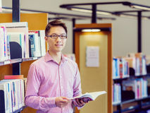 Happy male student holding books at the library. Happy male asian student holding books at the library Stock Images