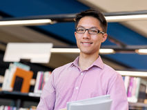 Happy male student holding books at the library. Happy male asian student holding books at the library Royalty Free Stock Images
