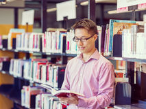 Happy male student holding books at the library. Happy male asian student holding books at the library Royalty Free Stock Image