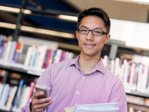 Happy male student holding books at the library. Happy male asian student holding books and his mobile at the library Royalty Free Stock Images