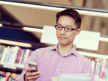 Happy male student holding books at the library. Happy male asian student holding books and his mobile at the library Royalty Free Stock Image