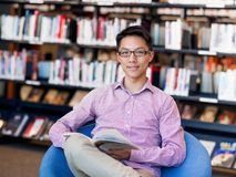 Happy male student holding books at the library. Happy male asian student holding books at the library Royalty Free Stock Photos