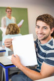 Happy male student holding paper. Portrait of happy male student holding paper in the class Stock Image