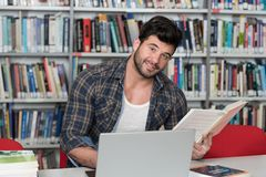Happy Male Student With Laptop in Library. Handsome Male Student With Laptop and Books Working in a High School Library Stock Images