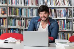 Happy Male Student With Laptop in Library. Handsome Male Student With Laptop and Books Working in a High School Library Stock Image