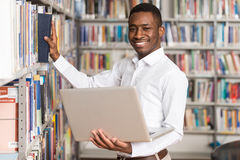 Happy Male Student With Laptop In Library Royalty Free Stock Photo