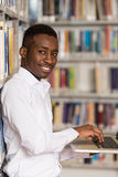 Happy Male Student With Laptop In Library. In The Library - Handsome Male Student With Laptop And Books Working In A High School - University Library - Shallow Stock Image
