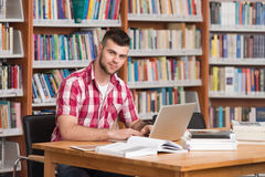 Happy Male Student With Laptop In Library Stock Photos