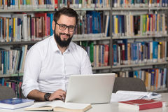 Happy Male Student With Laptop In Library Royalty Free Stock Image