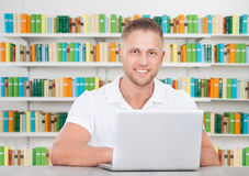 Happy Male Student With Laptop In Library. Portrait of happy male student sitting with laptop at desk in library Royalty Free Stock Image