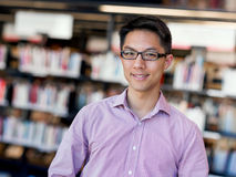 Happy male student at the library. Happy male asian student wearing glasses standing at the library Royalty Free Stock Images