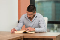 Happy Male Student In Library With Book. A Portrait Of An Caucasian College Student Man In Library - Shallow Depth Of Field Stock Images