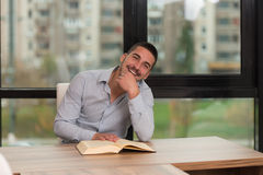 Happy Male Student In Library With Book. A Portrait Of An Caucasian College Student Man In Library - Shallow Depth Of Field Stock Photography