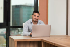Happy Male Student In Library With Laptop. In The Library - Handsome Male Student With Laptop And Books Working In A High School - University Library - Shallow Royalty Free Stock Image