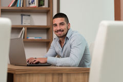 Happy Male Student In Library With Laptop. In The Library - Handsome Male Student With Laptop And Books Working In A High School - University Library - Shallow Stock Photos