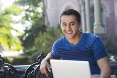 Happy male student outdoors with a laptop. Happy young man sitting outdoors with a laptop Stock Images