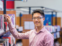 Happy male student picking up books at the library. Happy male asian student holding books at the library Royalty Free Stock Images