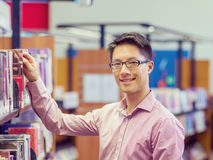 Happy male student picking up books at the library. Happy male asian student holding books at the library Royalty Free Stock Photos