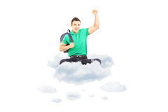 Happy male student sitting on a cloud with raised hand gesturing. Happiness isolated on white background Royalty Free Stock Image
