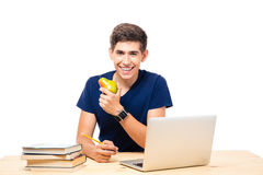 Happy male student sitting at the table with laptop. And holding pear isolated on a white background. Looking at camera Stock Images