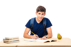 Happy male student sitting at the table. And writing in notebook isolated on a white background. Looking at camera Stock Images