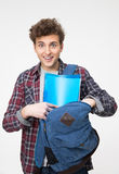 Happy male student standing with backpack. Over gray background Stock Photography