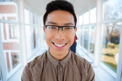 Happy male student standing in university hall Stock Image