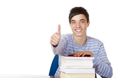 Happy male student with study books show thumb up. Young happy male student is smiling and leaning on his study books. Isolated on white Royalty Free Stock Image