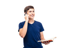 Happy male student talking on the phone. And holding book isolated on a white background Stock Photo