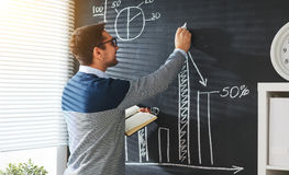 Happy male student, teacher, freelancer with chalk at blackboard. Happy male student, teacher, freelancer with chalk at the blackboard royalty free stock image