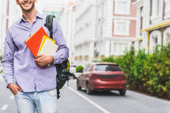 Happy male student with textbooks on street Stock Photos