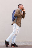 Happy male student walking with cell phone and bag. Full body side portrait of happy male student walking with cell phone and bag Royalty Free Stock Photos