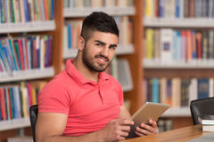 Happy Male Student Working With Laptop In Library Stock Photo