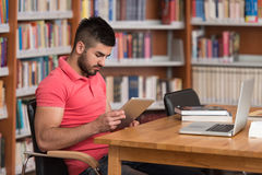 Happy Male Student Working With Laptop In Library Stock Images