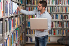 Happy Male Student Working With Laptop In Library. In The Library - Handsome Male Student With Laptop And Books Working In A High School - University Library Royalty Free Stock Image