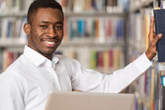 Happy Male Student Working With Laptop In Library. In The Library - Handsome Male Student With Laptop And Books Working In A High School - University Library Royalty Free Stock Photo