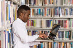 Happy Male Student Working With Laptop In Library Stock Photography