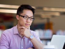 Happy male student working at the library. Happy male asian student working at the library Royalty Free Stock Images