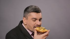 Happy male in suit eating a piece of tasty pizza at work, fat unhealthy food. Stock footage stock footage