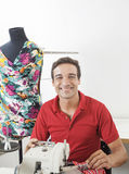 Happy Male Tailor Sitting By Mannequin In Sewing Factory Royalty Free Stock Images