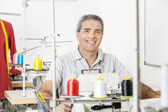 Happy Male Tailor Sitting In Sewing Factory Stock Photo