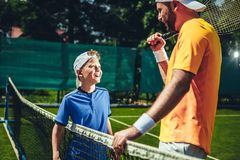 Happy male talking with kid on court stock photos