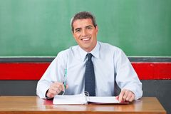 Happy Male Teacher With Pen And Binder Sitting At. Portrait of happy mature male teacher sitting with binder and pen at desk in classroom Stock Image