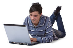 Happy male teenager on floor with computer laptop Stock Photography