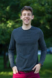 Happy male teenager in grey shirt outdoors. Happy smiling male teenager with in grey long sleeve shirt outdoors park stock image