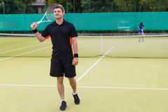 Happy male tennis player holding a racket on his shoulder after. Happy male tennis player wearing a sportswear and holding a racket on his shoulder after a match Royalty Free Stock Photos