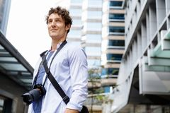 Male tourist in city. Happy male tourist in city walking with camera Stock Image