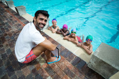 Happy male trainer with little swimmers at poolside. Portrait of happy male trainer with little swimmers at poolside Royalty Free Stock Photos