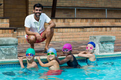Happy male trainer with little swimmers at poolside. Portrait of happy male trainer with little swimmers at poolside Stock Image